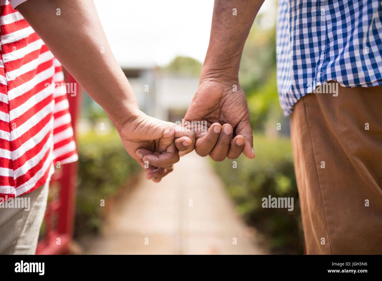 Imagen recortada de alto par la celebración de dedos pequeños mientras está de pie en el patio Foto de stock
