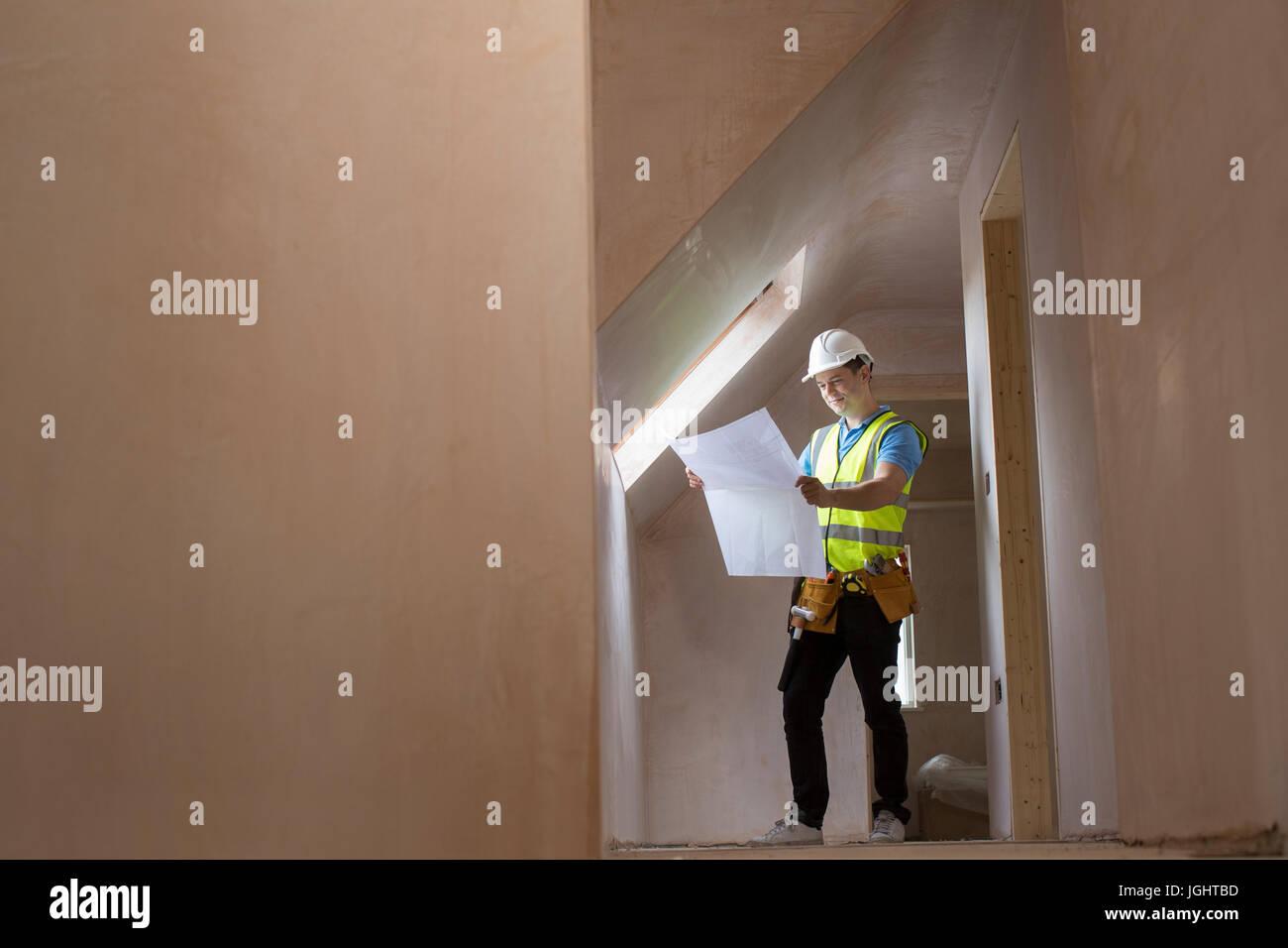 Arquitecto en sitio de construcción contemplando planes de casa Imagen De Stock