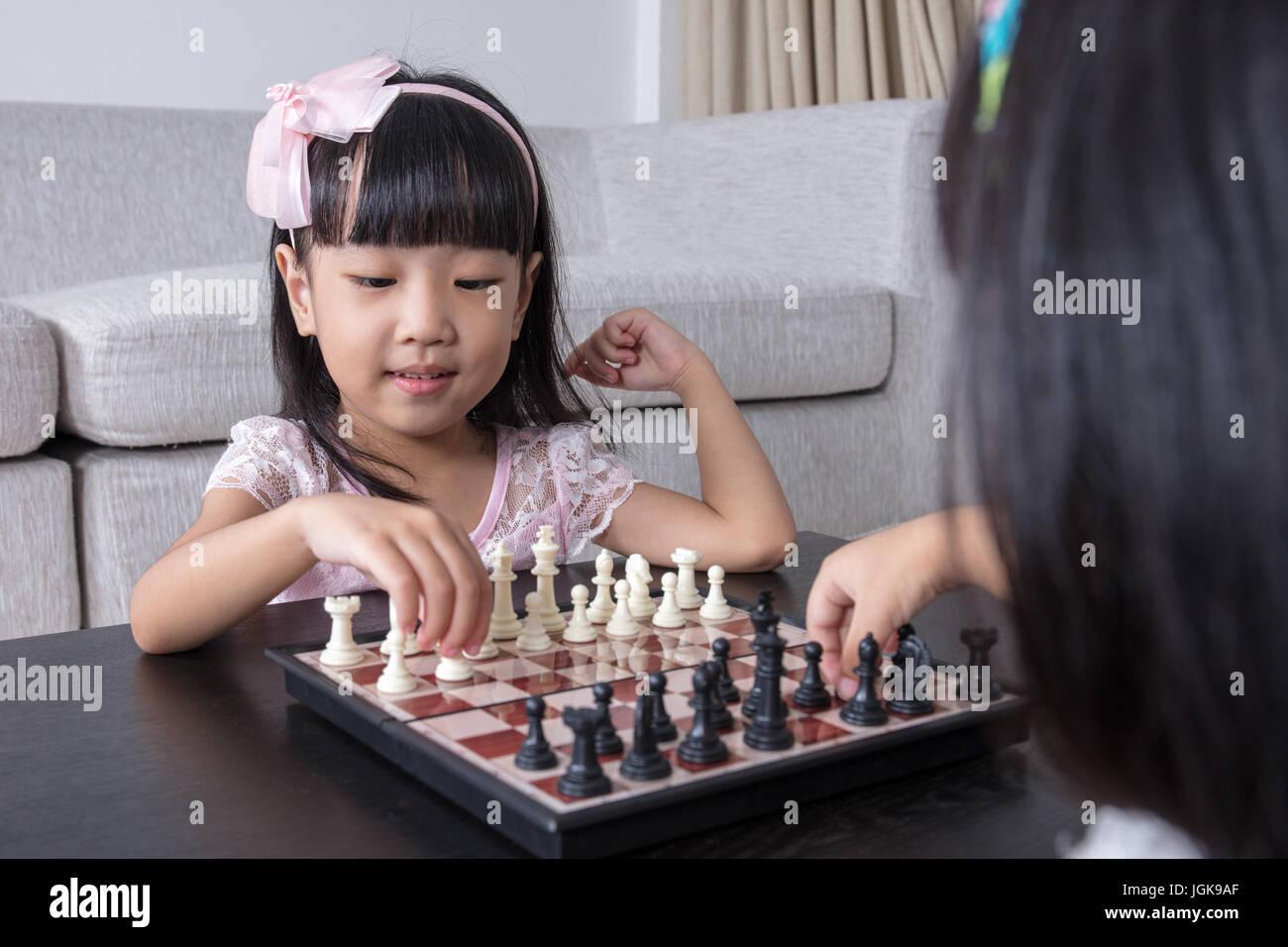 Chino Asia hermanitas jugando ajedrez juntos en el salón de casa. Foto de stock