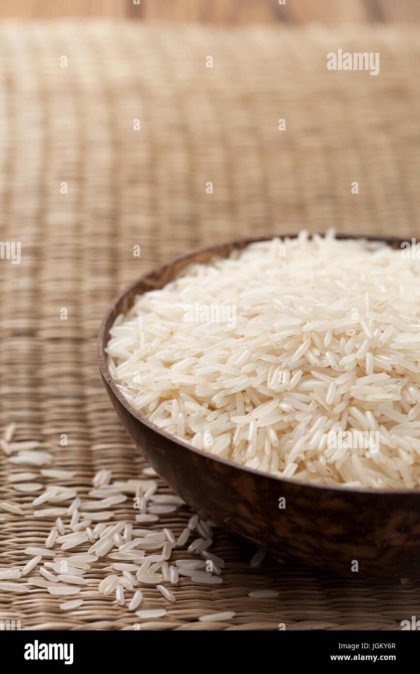 El arroz Basmati en tazón de madera sobre fondo de paja Imagen De Stock