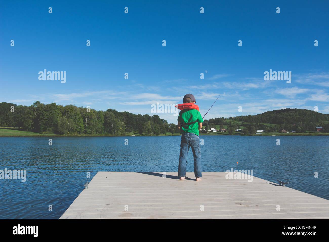 Un niño pesca en un muelle en un estanque en una zona rural. Imagen De Stock