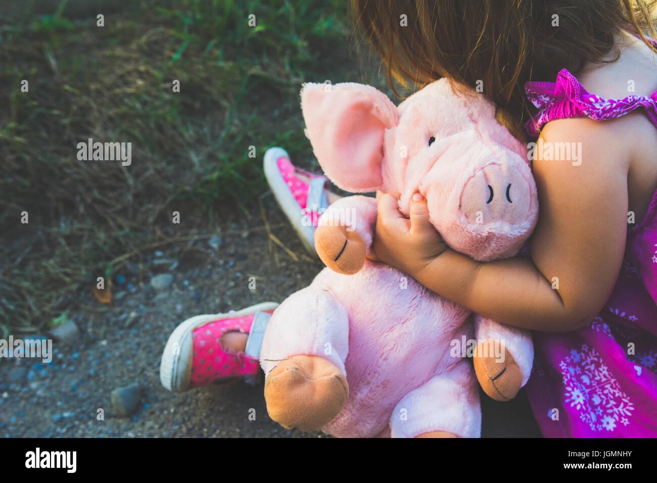 Una niña sostiene un peluche rosa rosa Foto de stock