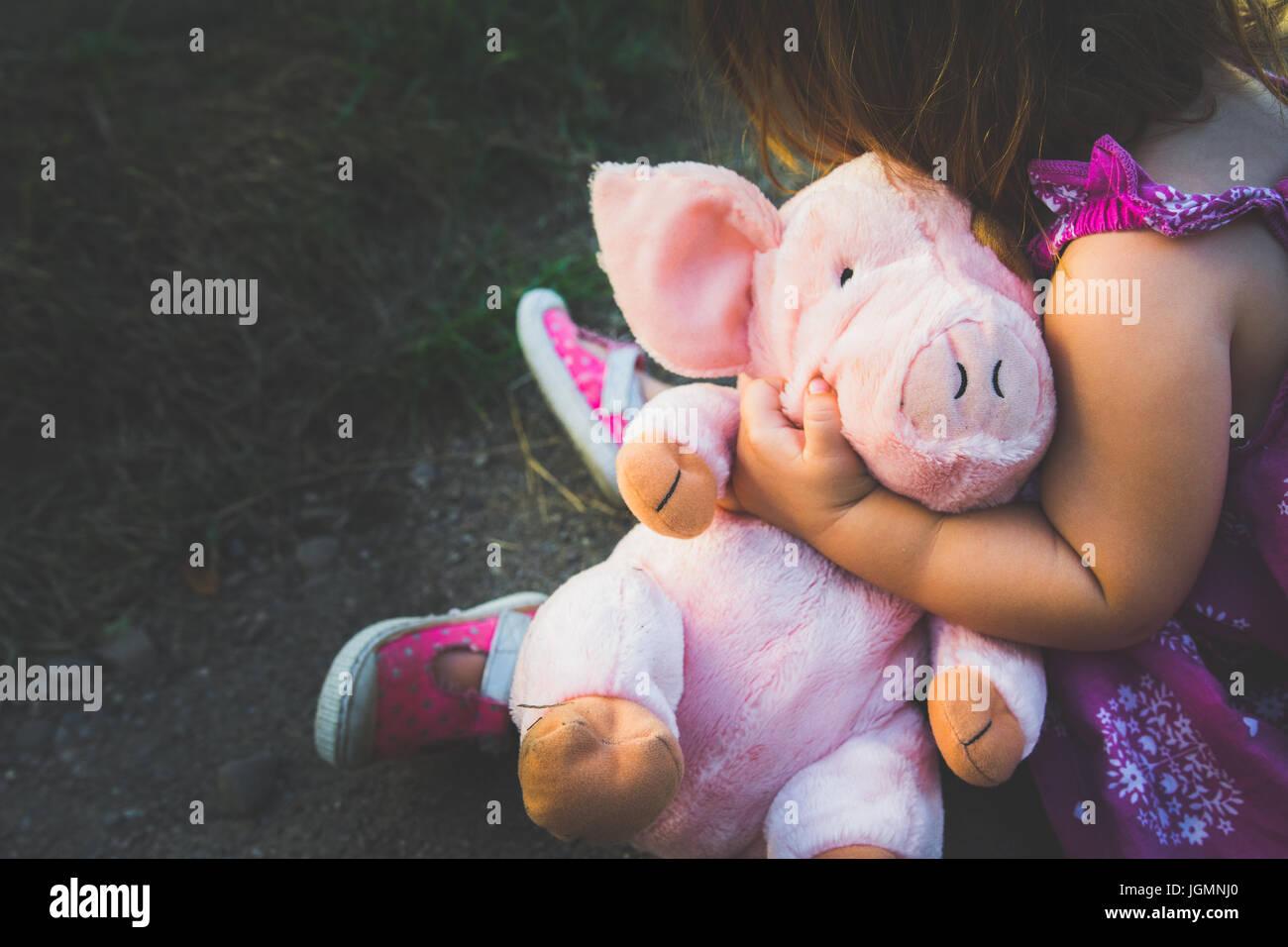 Un joven niño posee un cerdo de peluche rosa. Imagen De Stock