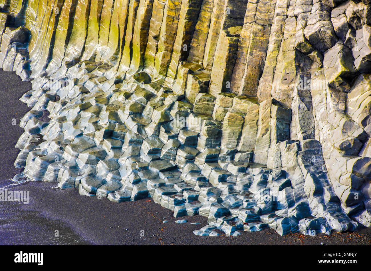 Grandes rocas basálticas con musgo amarillo y azul en la playa Foto de stock