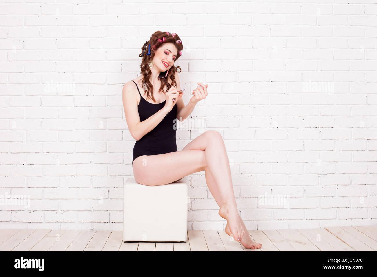 Chica con rizadores de pelo hablar por teléfono y pintar uñas Imagen De Stock