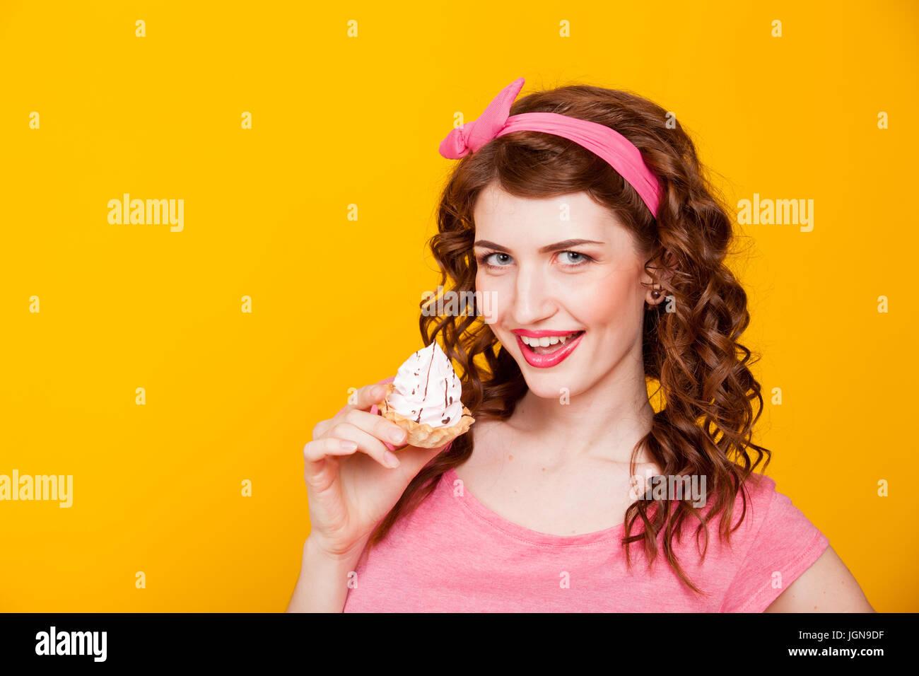 a047fc354 Chica en vestido rosado estilo pinup come torta con crema Imagen De Stock