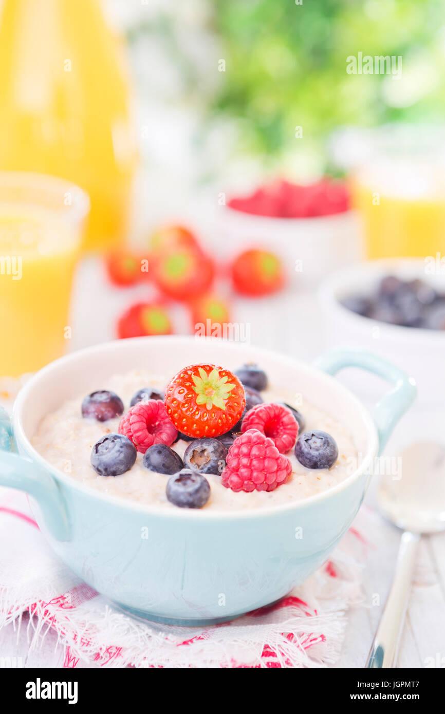 Un recipiente casero con gachas de avena con fruta fresca en una rústica mesa al aire libre. Imagen De Stock