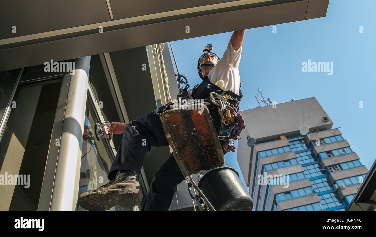 Escalada Industrial - Servicio de limpieza de la fachada. Los trabajadores colgando de cuerdas de escalada. Imagen De Stock