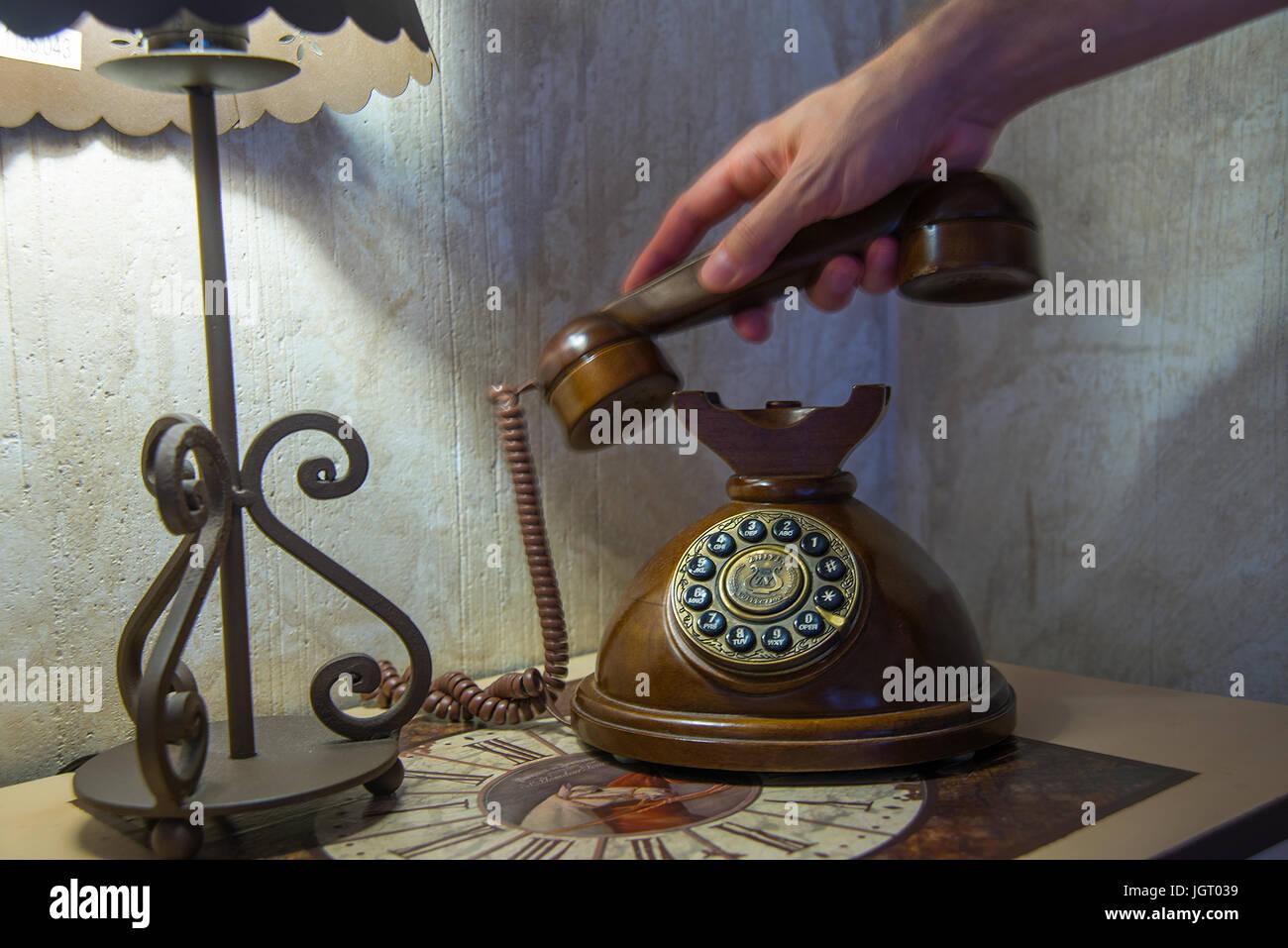 La mano del hombre descolgar el auricular de un teléfono antiguo. Foto de stock