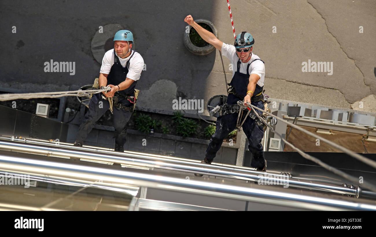 Los trabajadores colgando de cuerdas de escalada, mostrando signos de puño levantado. Imagen De Stock
