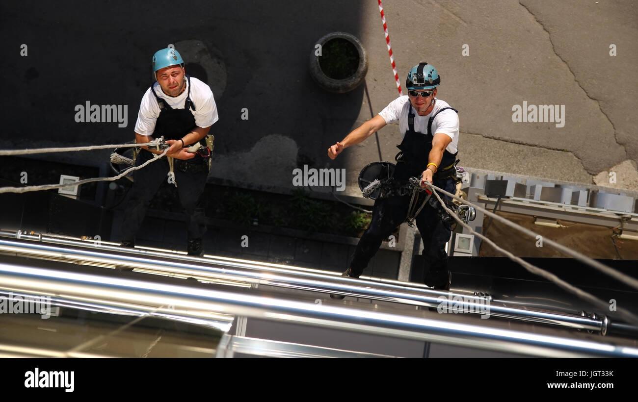 Los trabajadores colgando de cuerdas de escalada, mostrando el pulgar hacia arriba firmar. Imagen De Stock