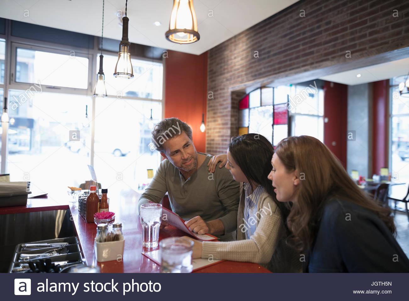 Padres e hija adolescente busca en menú, cenando en el comedor counter Imagen De Stock