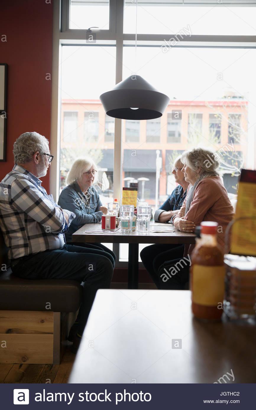 Altos amigos cenando en diner booth Imagen De Stock