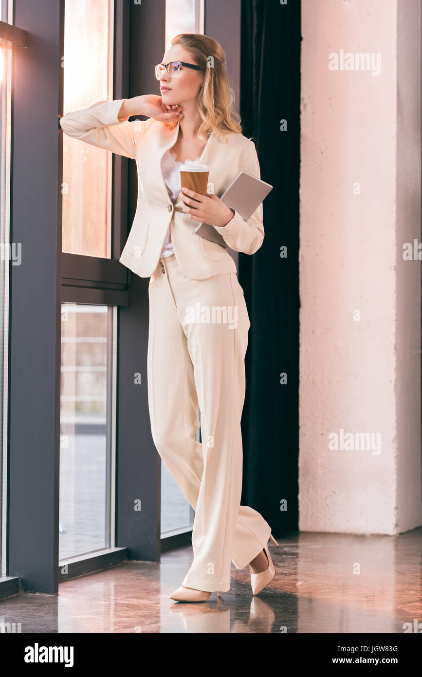 Joven Empresaria en traje de oficina permanente y la celebración de la taza de café y tableta digital Foto de stock
