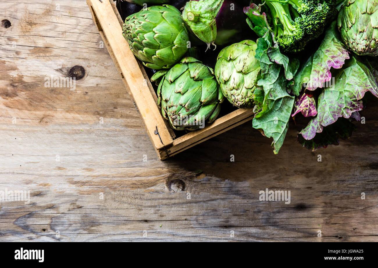 Concepto de cosecha de fondo de cocción. Verduras verdes frescas orgánicas en caja de madera Imagen De Stock