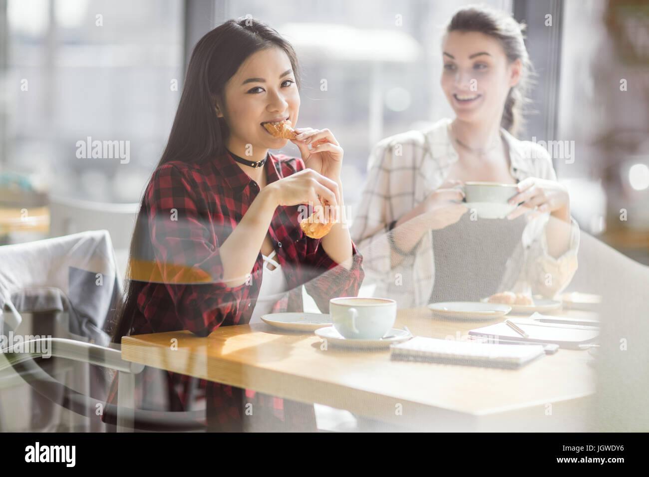 Las niñas comer cruasanes y bebiendo café en el cafe, coffee break Imagen De Stock