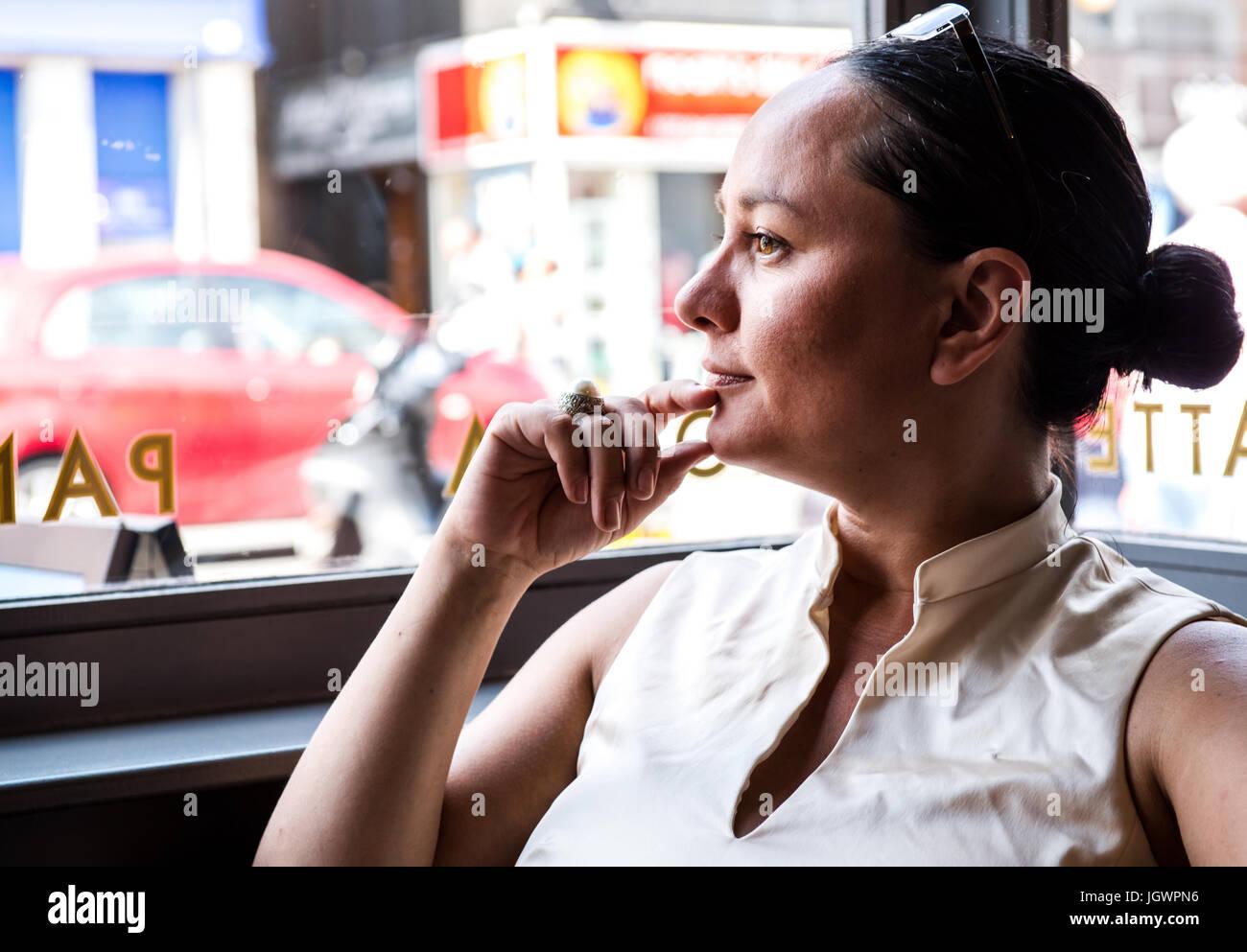 La empresaria con la mano en el mentón en el café bar Foto de stock