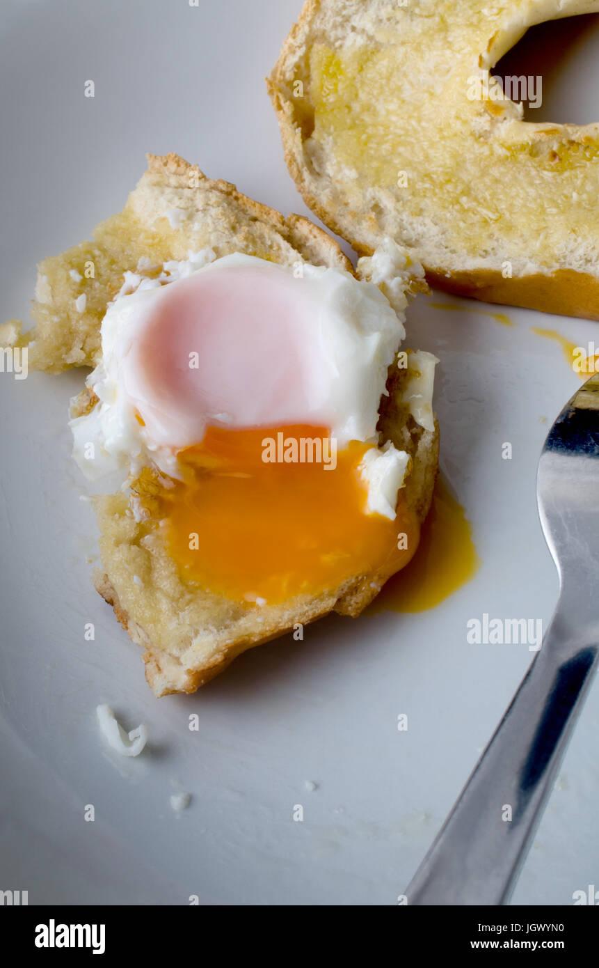Parcialmente comido intervalo libre de huevo frito con la yema de huevo y bagel extendiéndose por debajo de Imagen De Stock