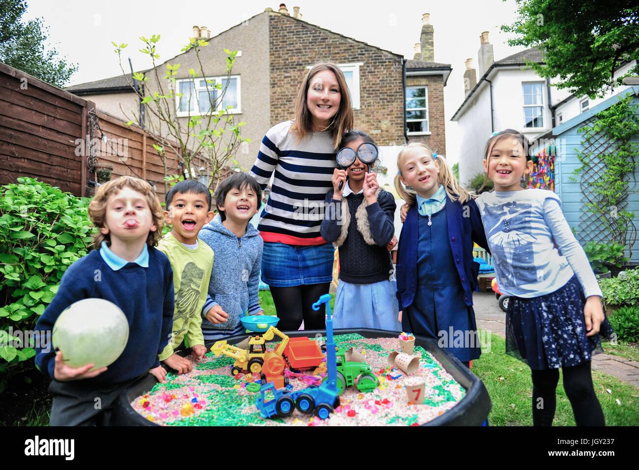 Retrato de childminder y niños por arenero mirando a la cámara sonriendo Imagen De Stock