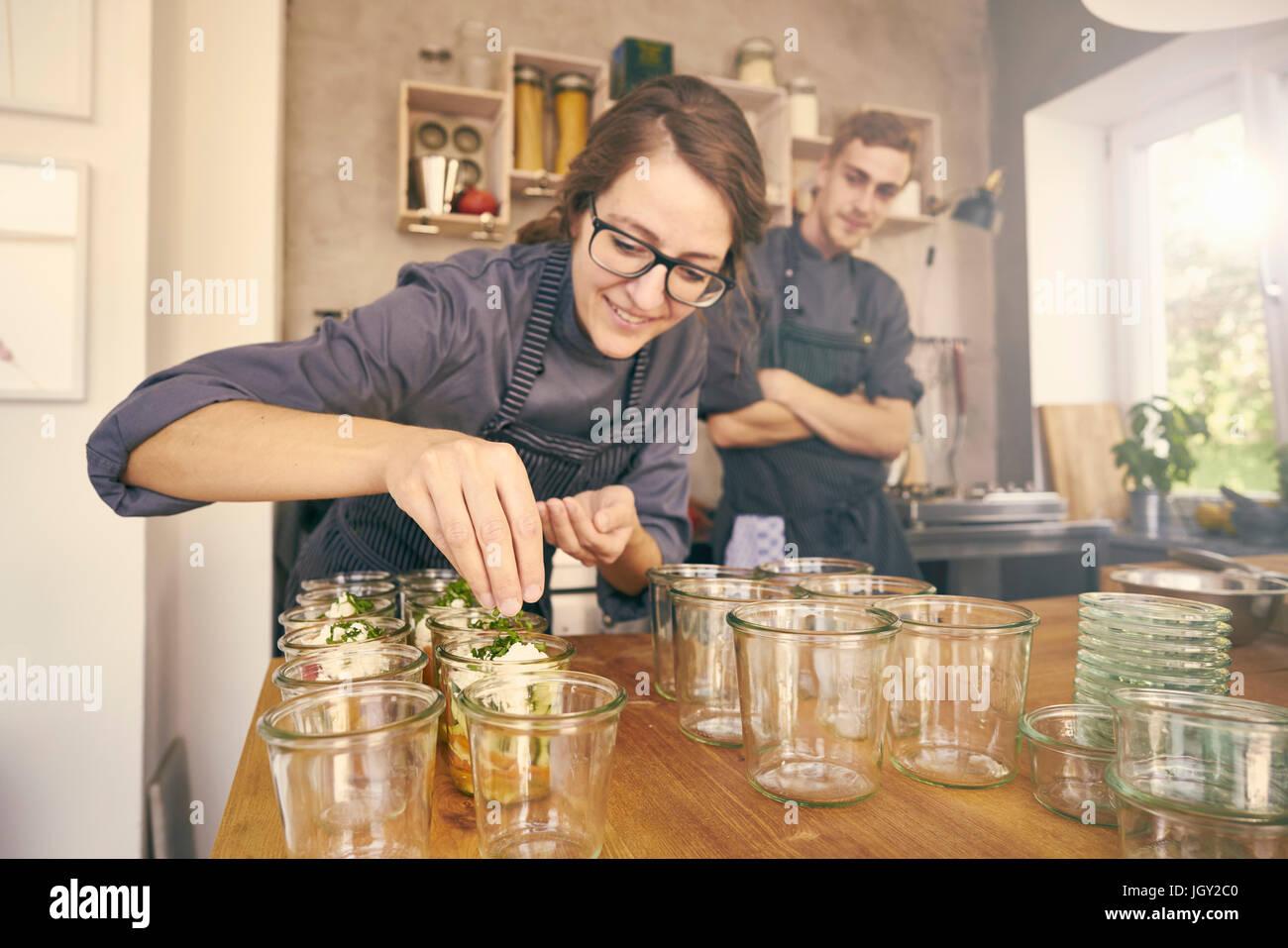 Chef llenando recipientes plásticos con porciones de comida Imagen De Stock