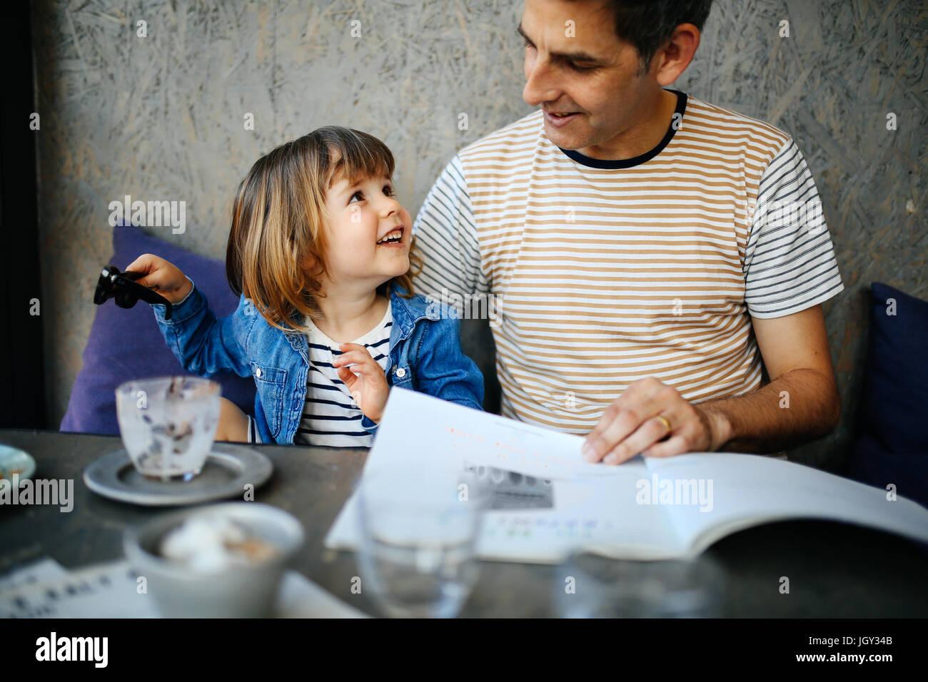 Niña jugando con gafas de sol del padre en el café Imagen De Stock