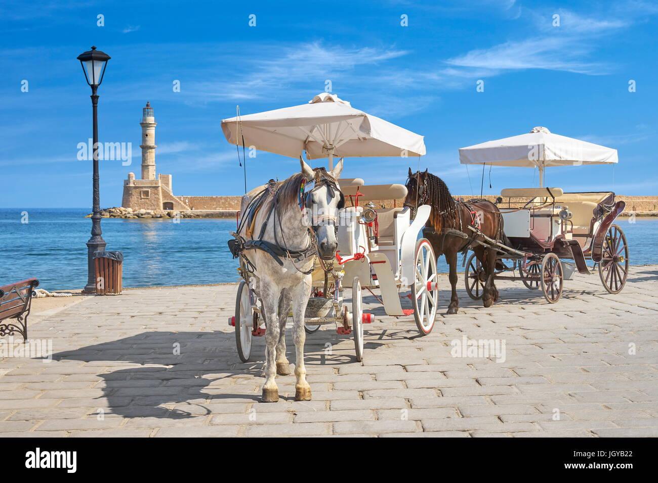 Carro con caballo, faro en el fondo, el casco antiguo de Chania, en la isla de Creta, Grecia Foto de stock