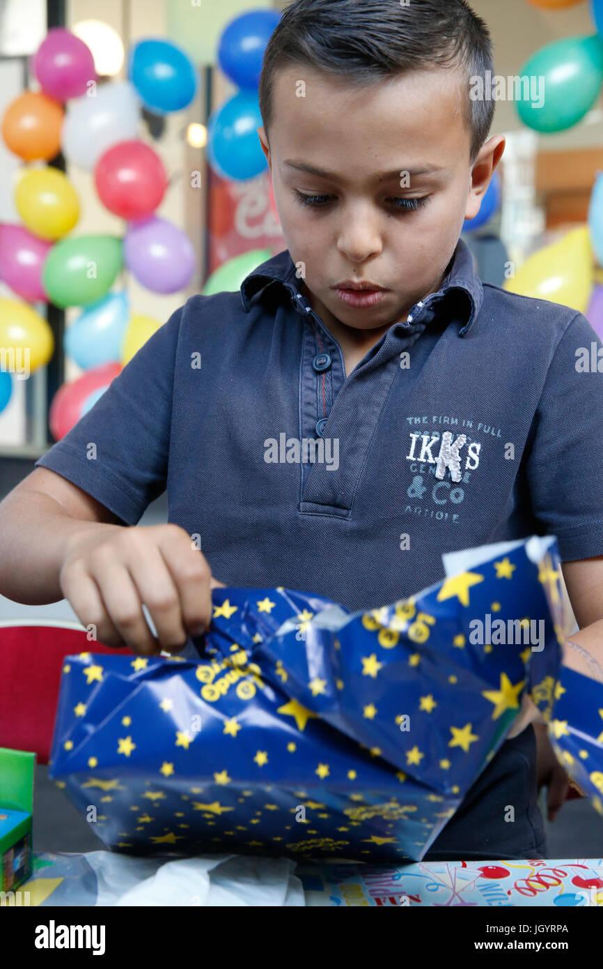 10-año-viejo muchacho desenvolver un regalo de cumpleaños. Francia. Imagen De Stock