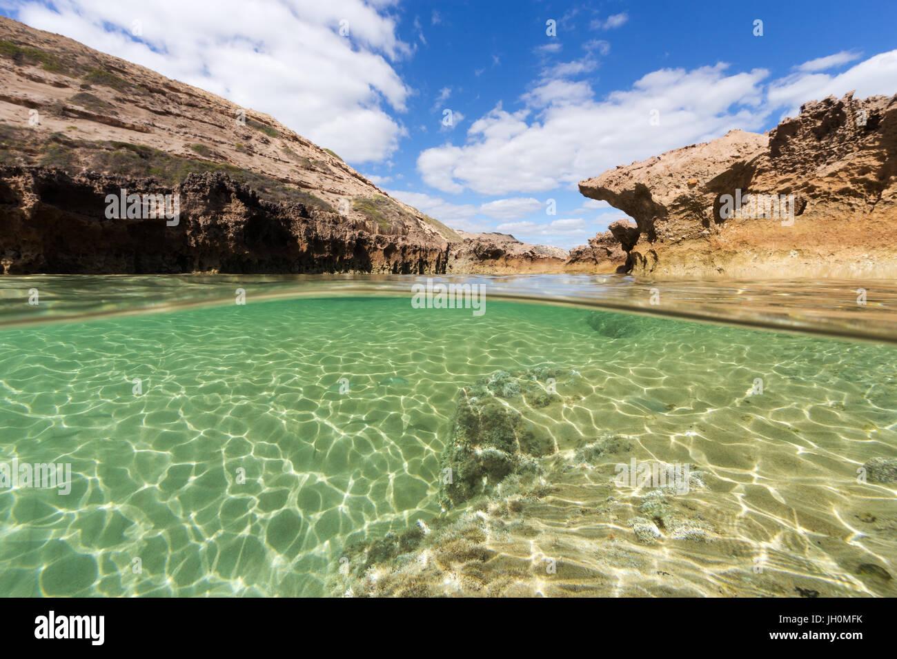 Un split shot de una prístina piscina de roca en una aislada en la costa sur de Australia. Imagen De Stock