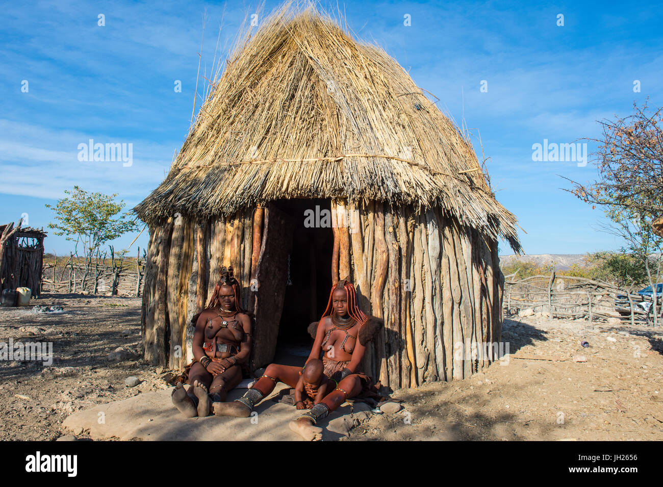 Las mujeres Himba delante de su cabaña, Kaokoland, Namibia, África Imagen De Stock