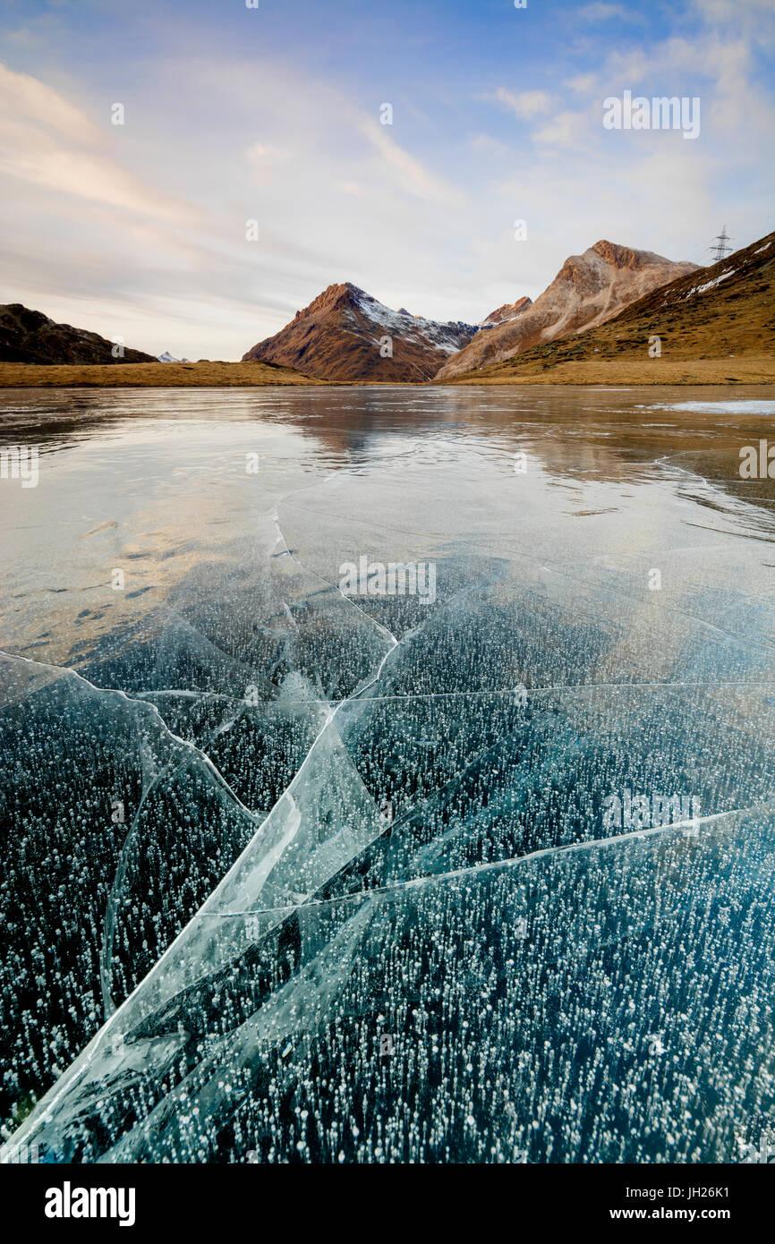 Atardecer en la congelada Lej Nair rodeado por picos rocosos, Bernina Pass, Cantón de Graubunden, Engadin, Suiza, Foto de stock