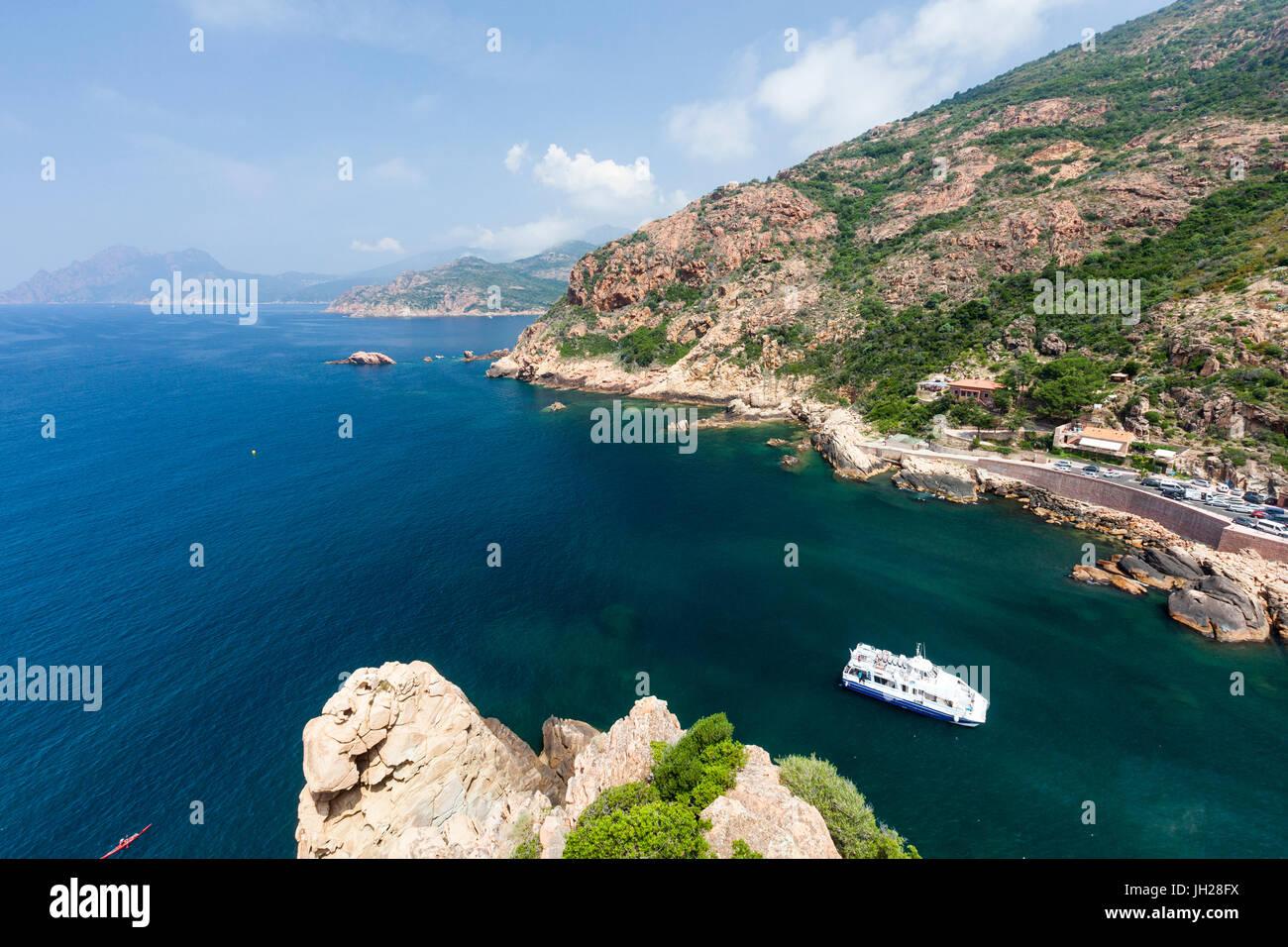 Barco turístico en el mar turquesa enmarcado por acantilados de piedra caliza, Porto, en el sur de Córcega, Imagen De Stock