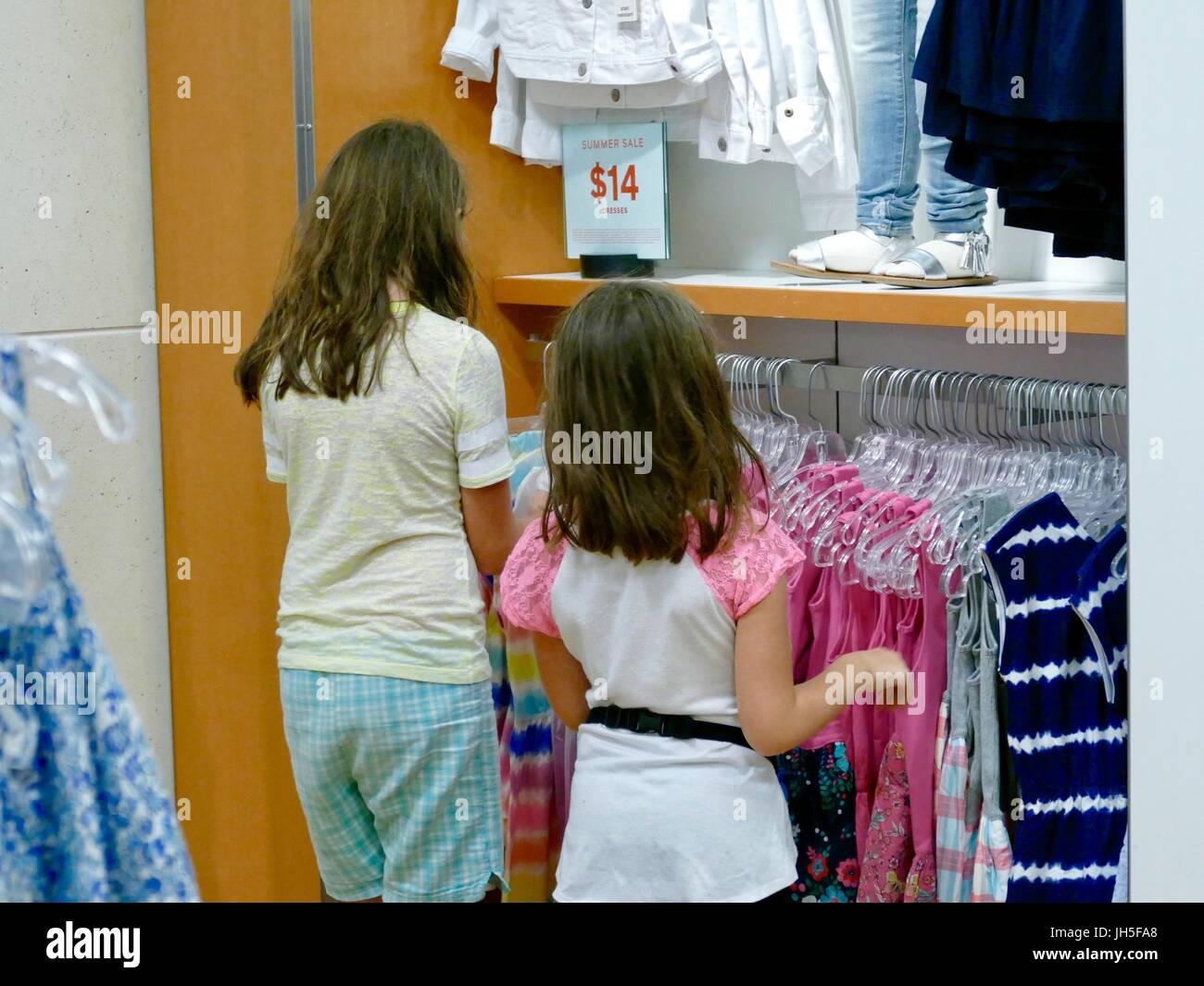 Las niñas de compras en el departamento de la infancia de una tienda de ropa al por menor. Florida, EE.UU. Imagen De Stock