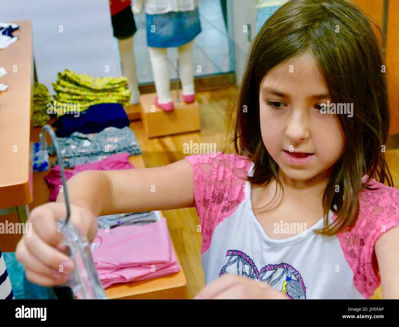 Niña de compras en el departamento de la infancia de una tienda de ropa al por menor en Florida, EE.UU. Imagen De Stock