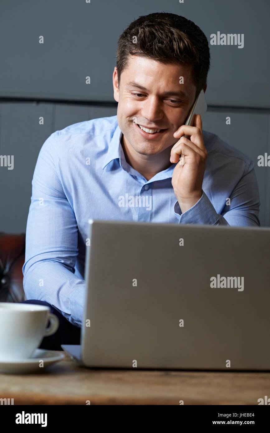 Hombre de negocios hablando por teléfono móvil trabajando en el portátil en Internet Cafe Imagen De Stock