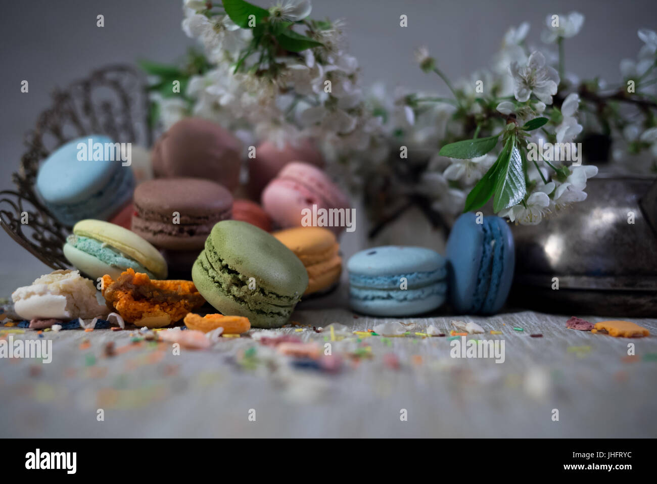 Macarons multicolor sobre una mesa con este jarrón y rama de cerezo en flor Imagen De Stock