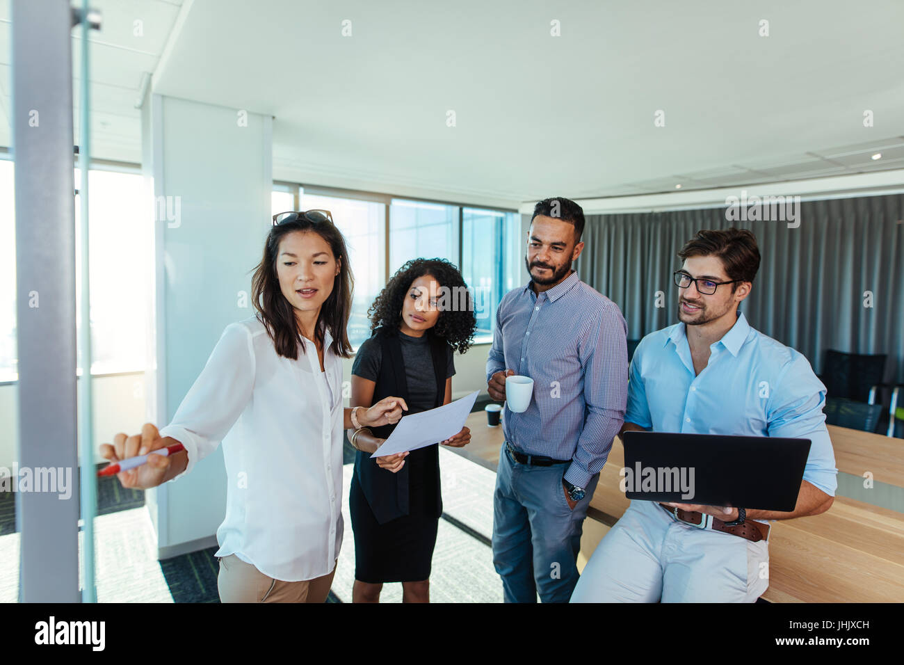 Inversores discutiendo un punto en la sala de juntas. Mujer de negocios apuntando hacia la junta mientras hace una Imagen De Stock