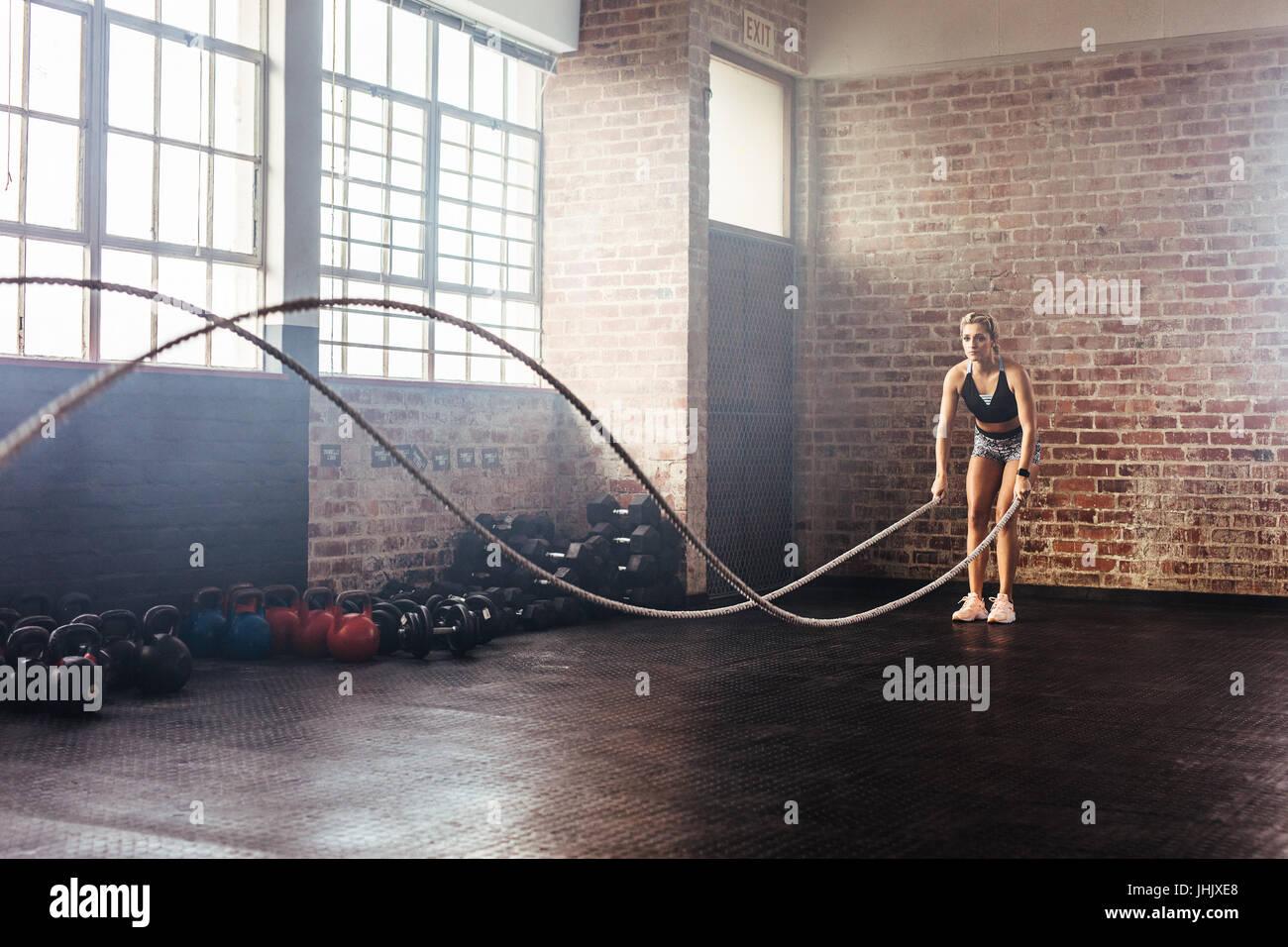 Mujer con cuerdas de capacitación para hacer ejercicio en el gimnasio. Atleta moviendo las cuerdas en el movimiento Imagen De Stock
