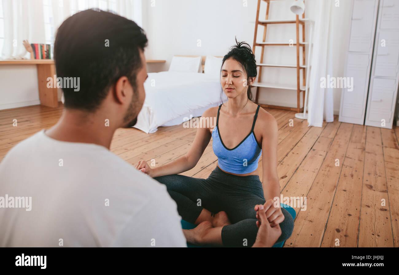 Hermosa joven hacer yoga en casa con su instructor. Pareja joven sentados juntos cogidos de la mano y practicar Imagen De Stock