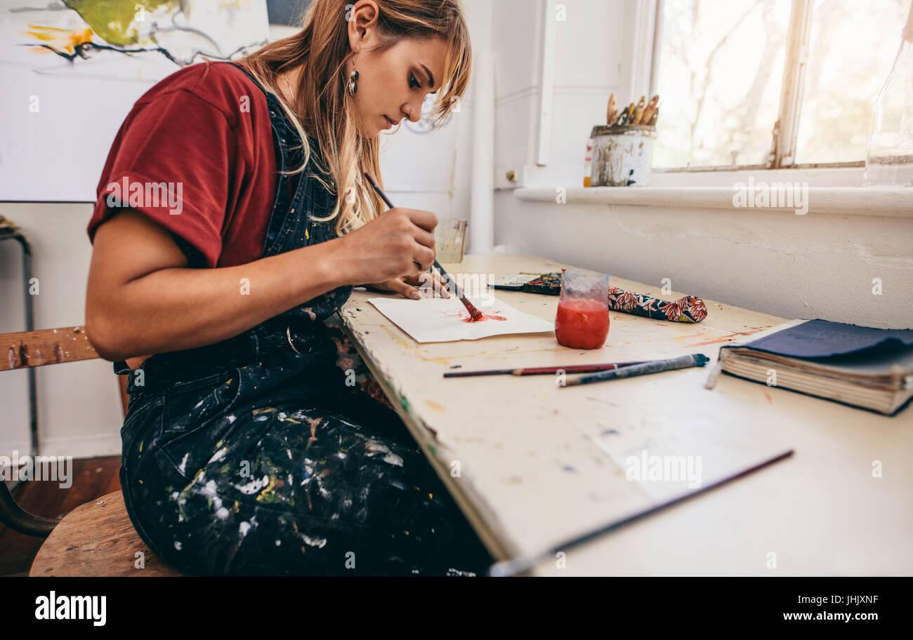 Vista lateral de la bella artista femenina dibujar imágenes en su taller. Mujer joven pintando en su estudio. Imagen De Stock