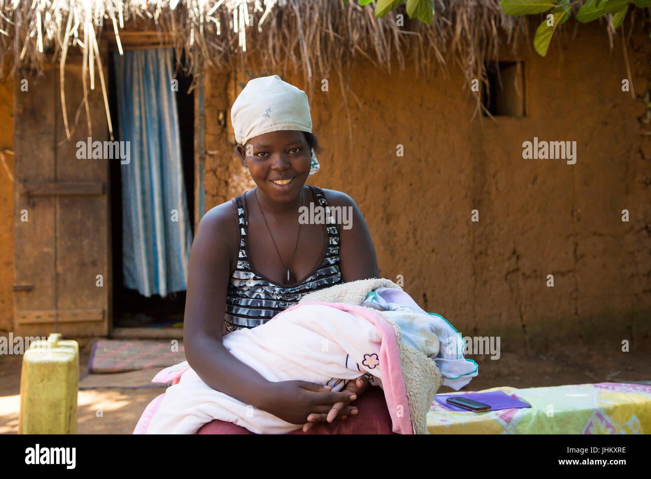 Una madre con su bebé recién nacido fuera de su choza de barro tradicional casa en Bukeeri, Uganda. Imagen De Stock