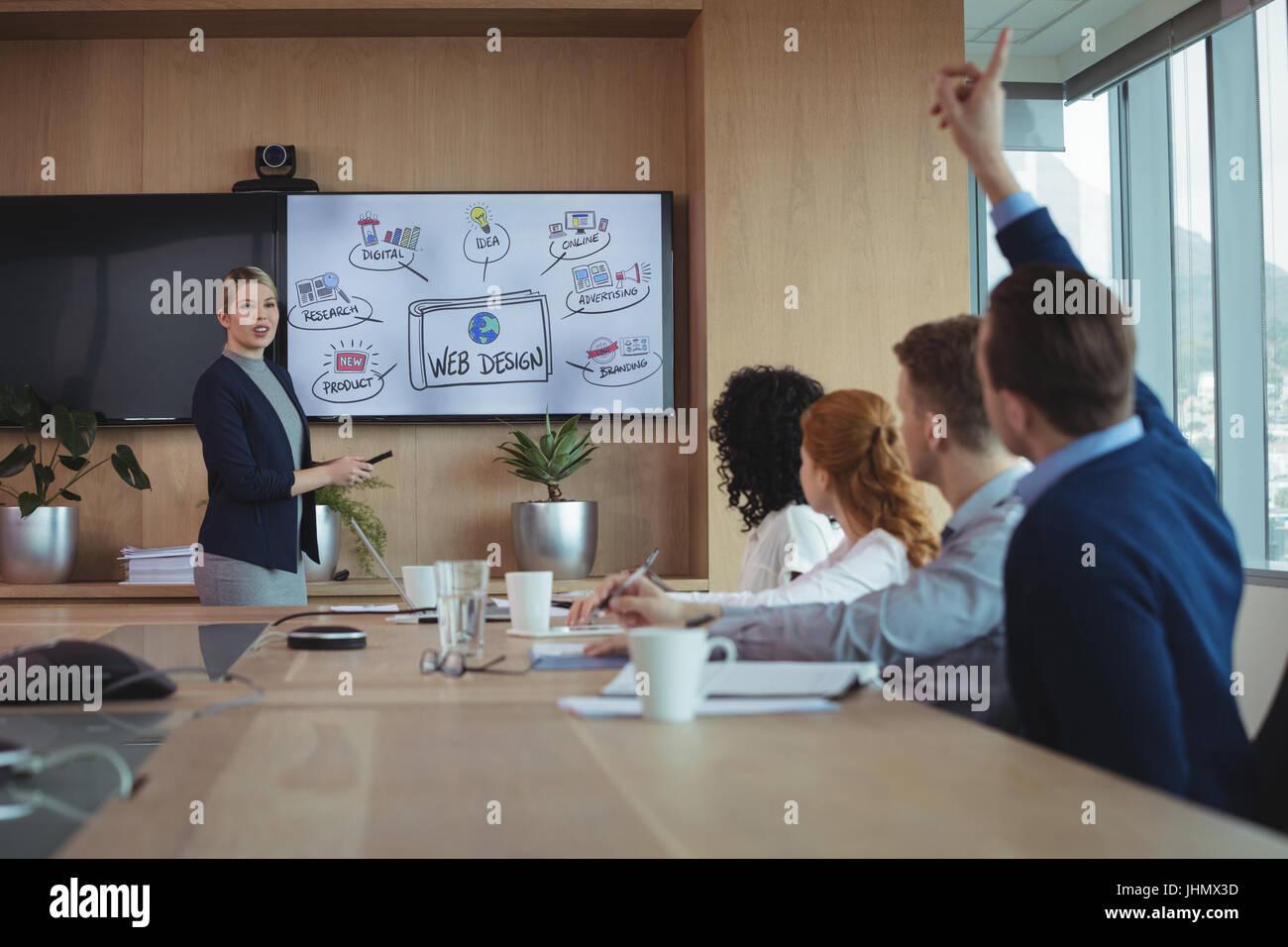 La empresaria interactuando con el equipo durante la reunión en la mesa de conferencias en la sala de la junta Imagen De Stock