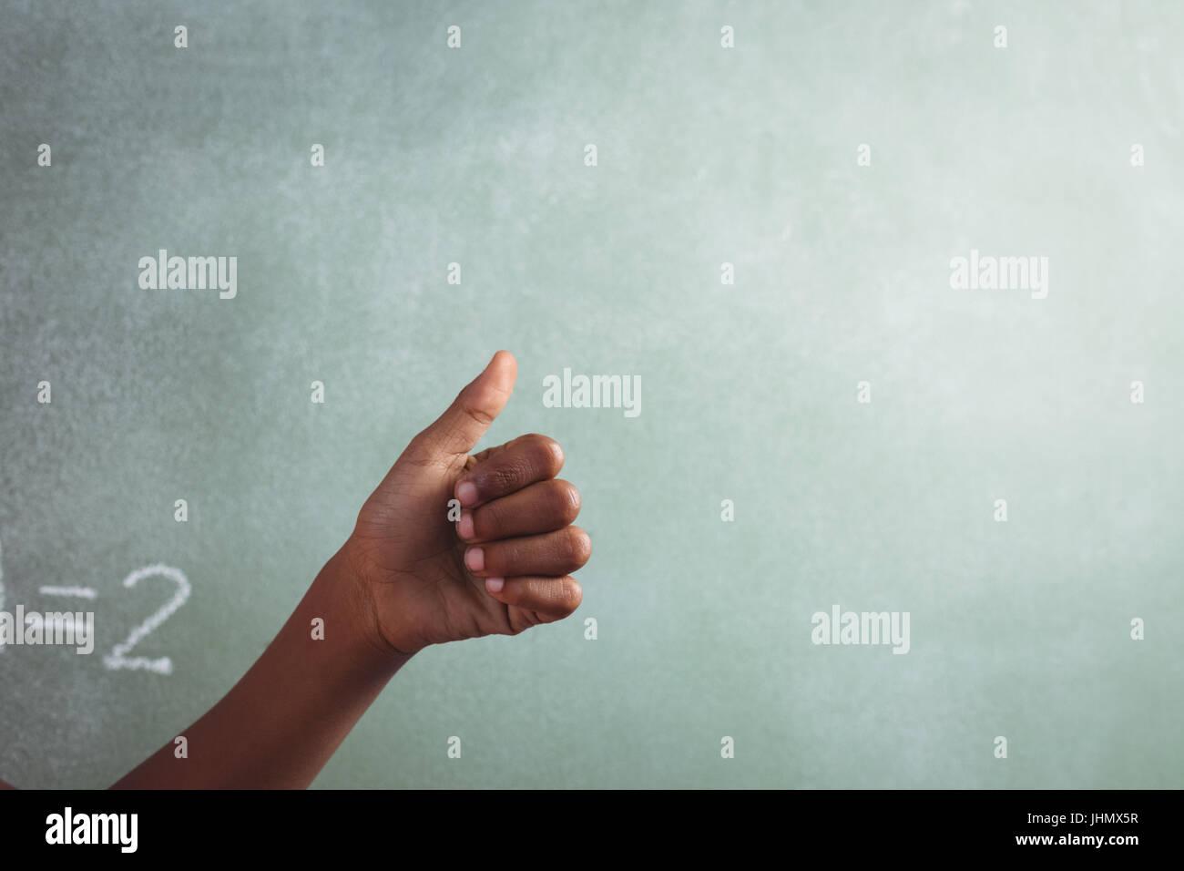 Mano recortada del estudiante mostrando el pulgar contra la pizarra en el aula Imagen De Stock