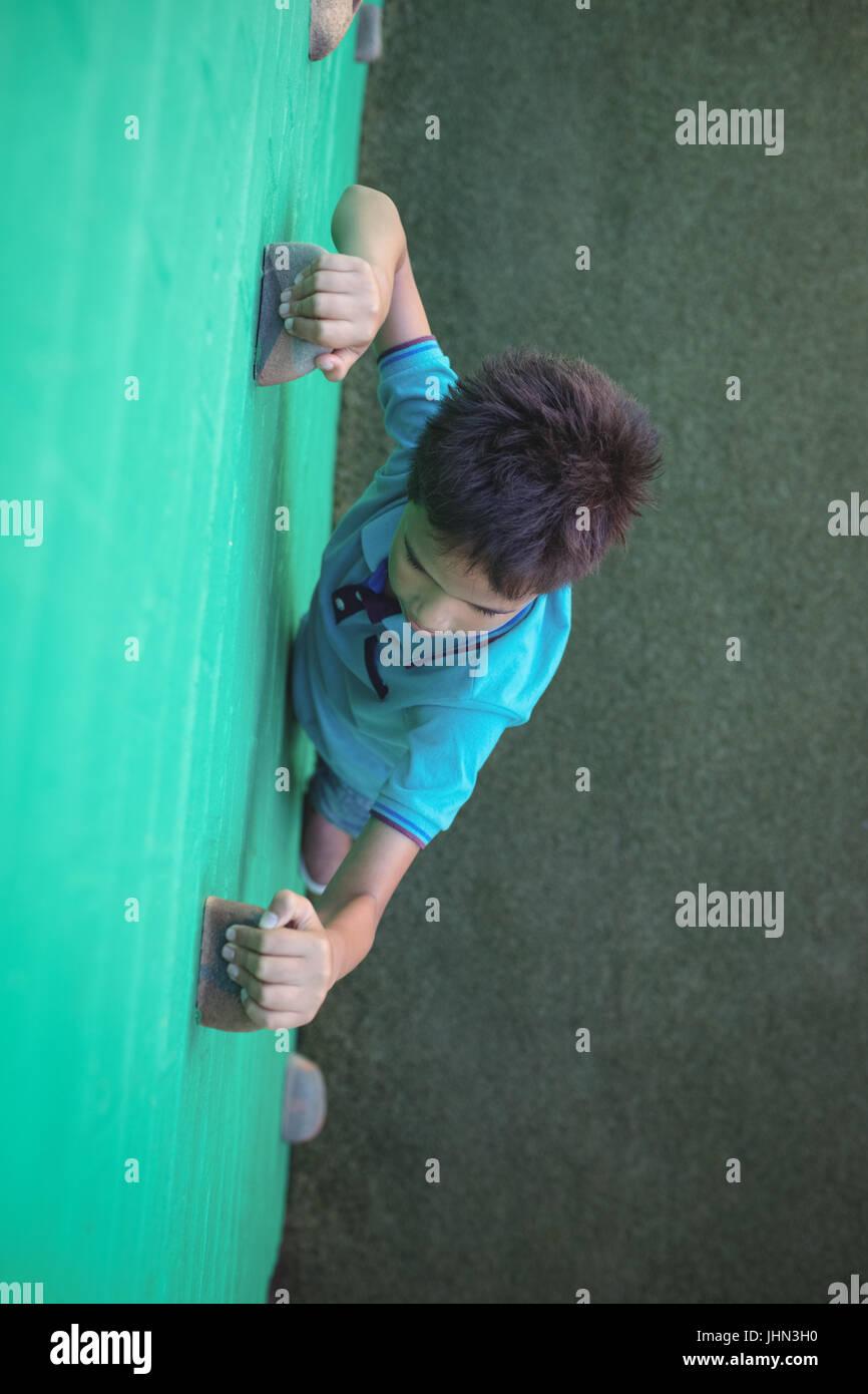 Un alto ángulo de visualización de boy apasionante escalada sostiene en la pared Imagen De Stock