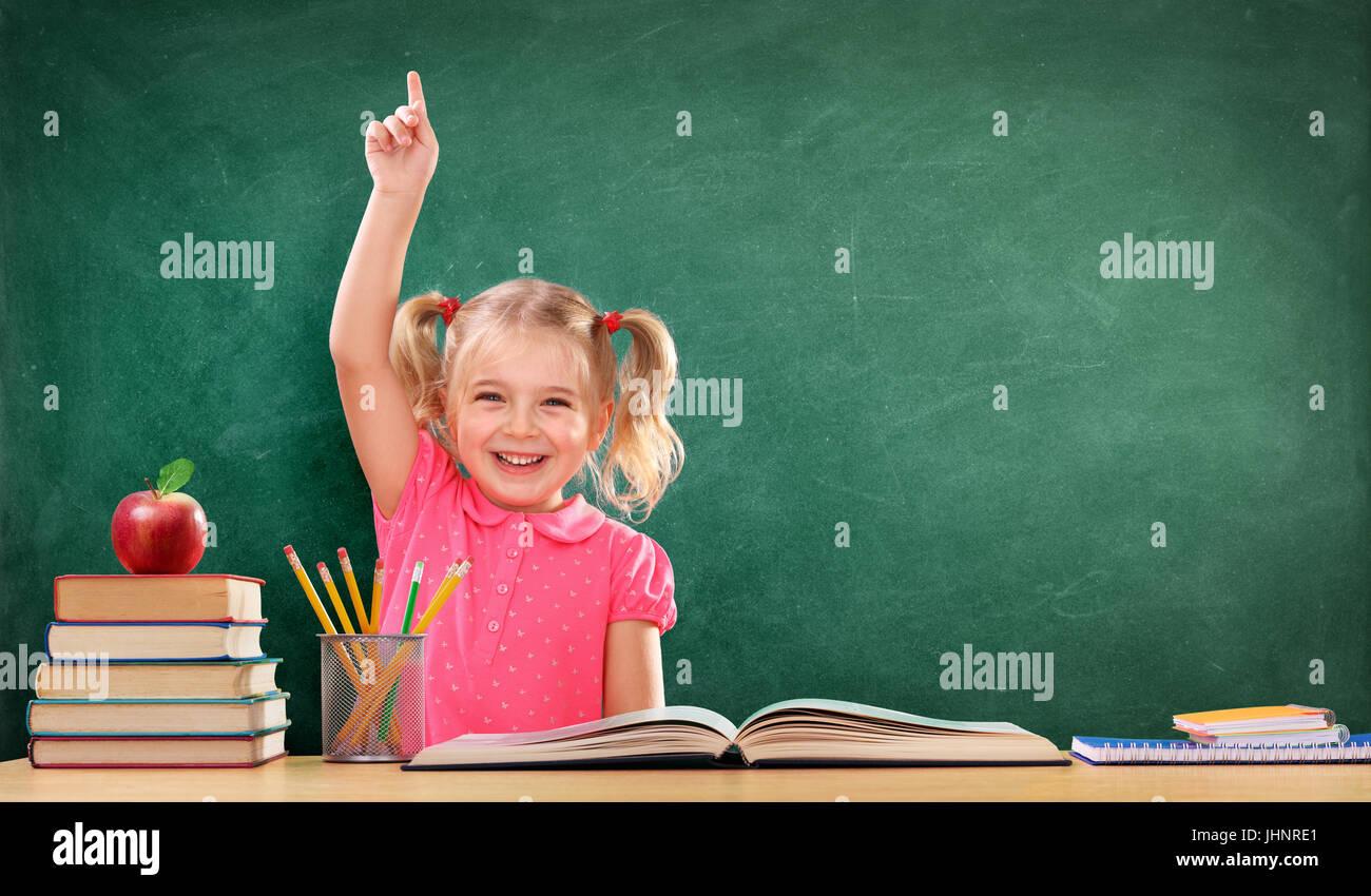 Feliz, la niña levantando la mano en el aula Imagen De Stock