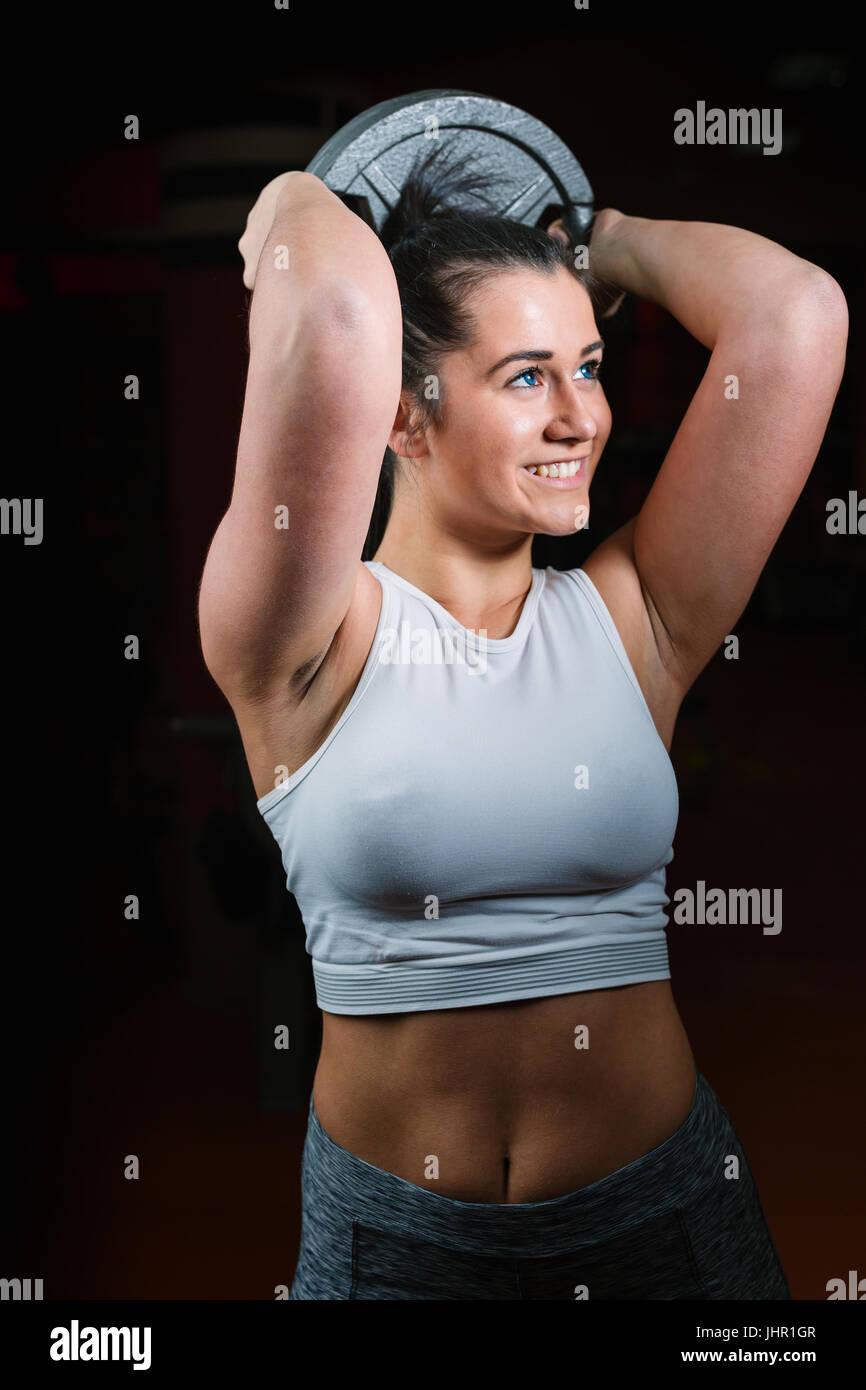 Fuerte joven con hermoso cuerpo atlético haciendo ejercicios con barbell. Fitness, culturismo. El cuidado de Imagen De Stock