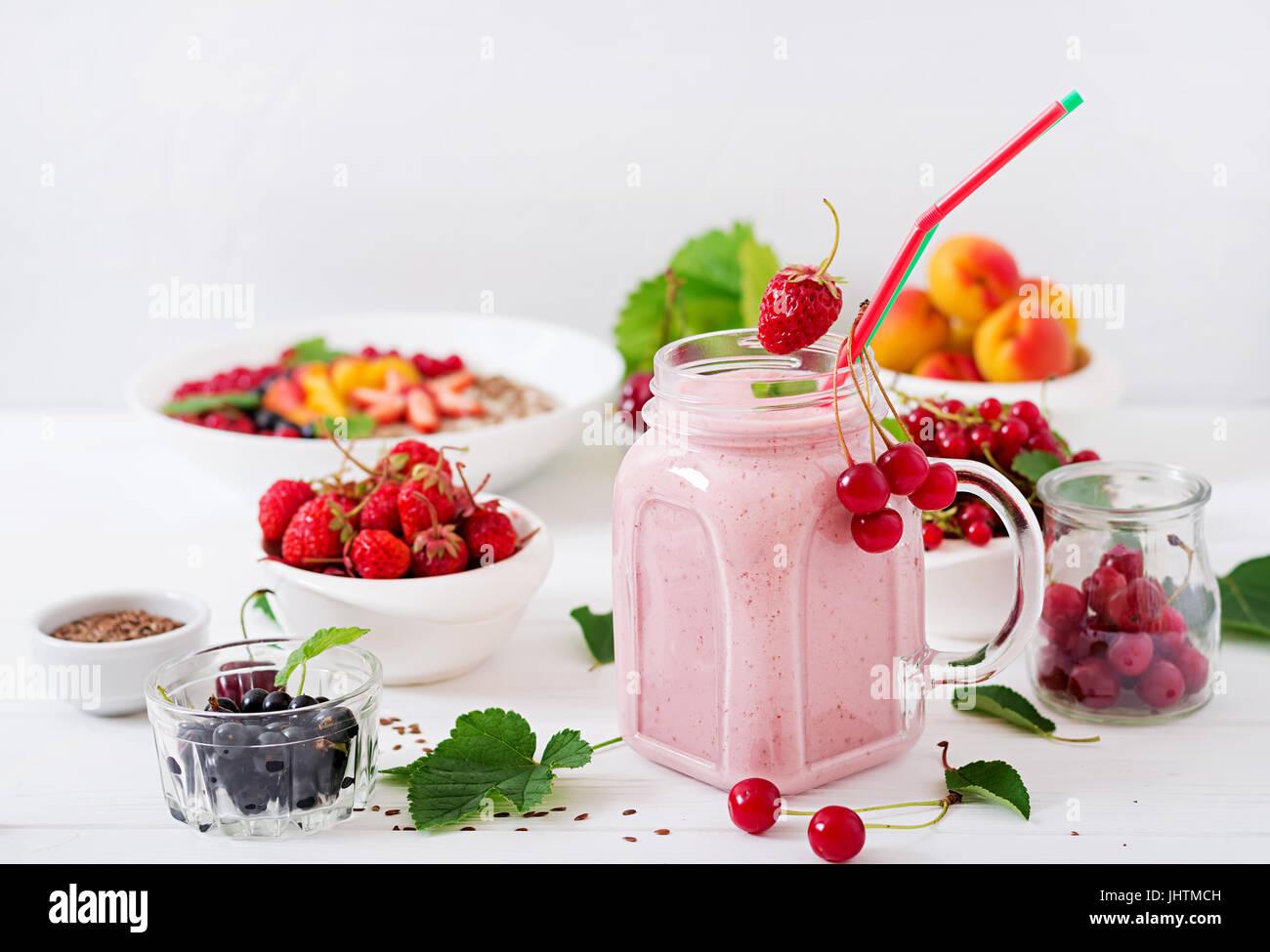 Yogures batidos de fresa en una jarra sobre un fondo blanco. Imagen De Stock