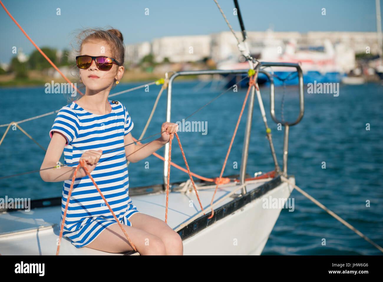 Hermosa niña slim en una camiseta de rayas y gafas de sol sentado a bordo  del 0bddc517851