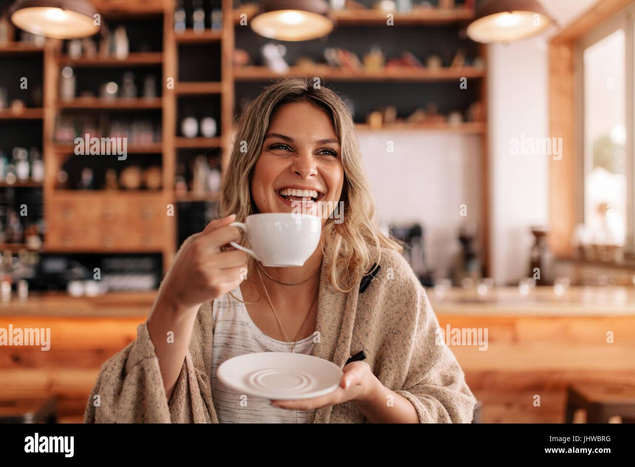 Retrato de joven y bella mujer de pie en un café y bebiendo café. Mujer sonriente con café en un Imagen De Stock