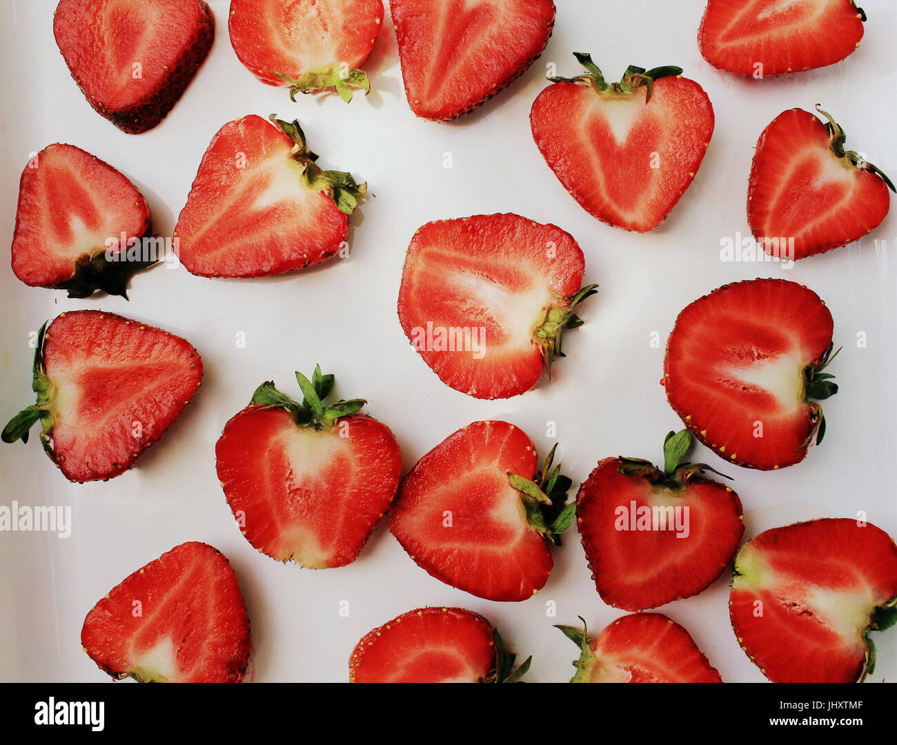 Fresa patrón creativo. Alimentos aislados como telón de fondo. Rodajas de bayas rojas maduras con hojas Imagen De Stock