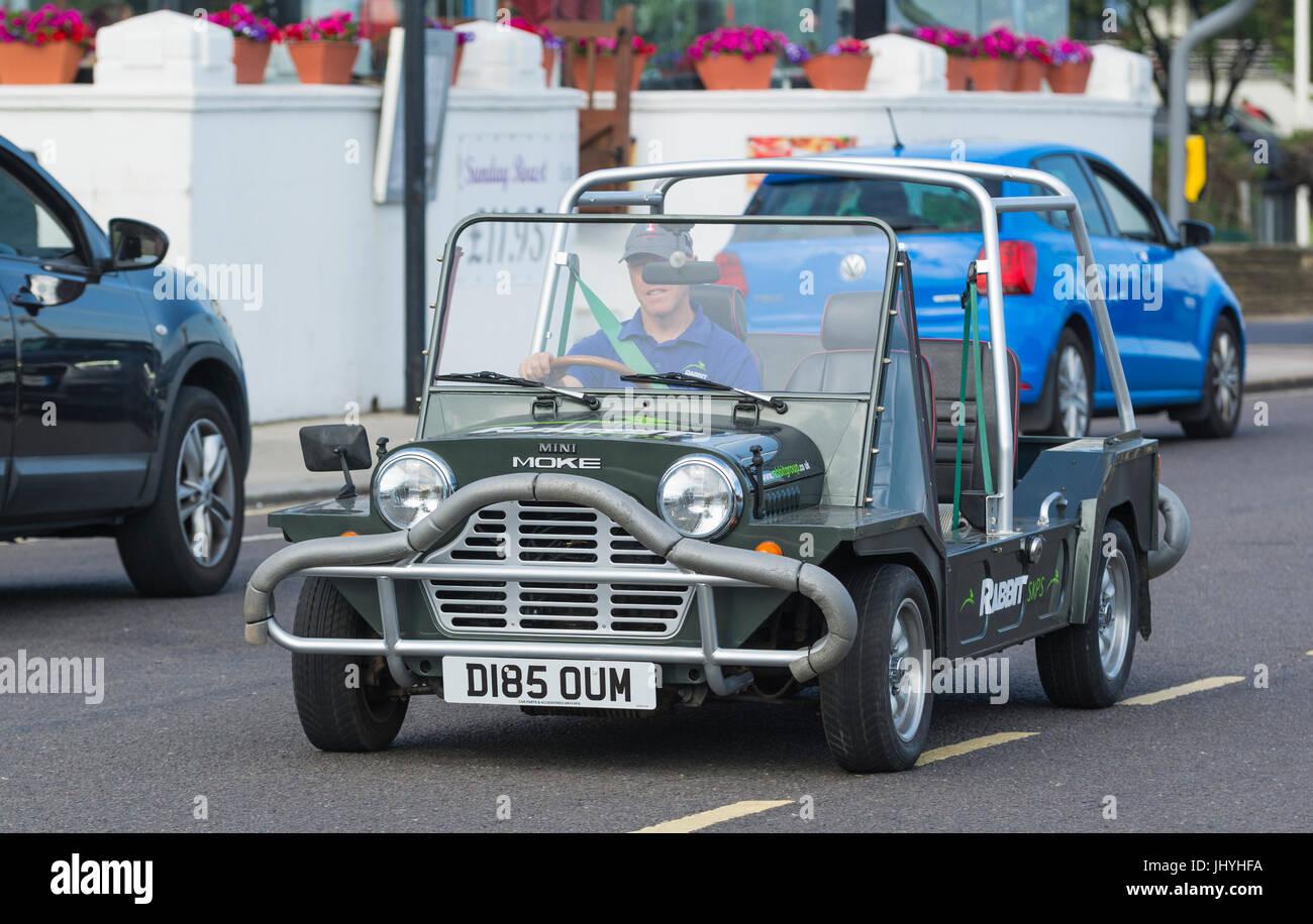 Mini Moke coche circulando por una carretera. Imagen De Stock